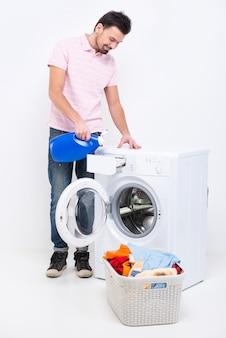 O homem novo feliz está fazendo a lavanderia em casa.