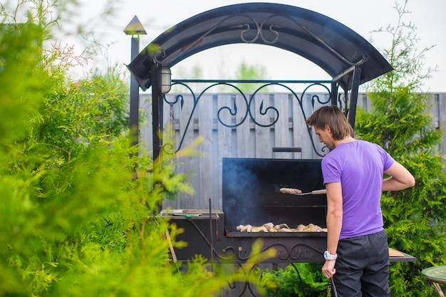 O homem novo frita bifes na grade ao ar livre em sua jarda