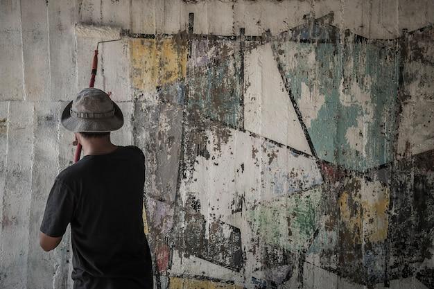 O homem novo limpa as paredes pintando o branco sobre a parede velha do cimento.