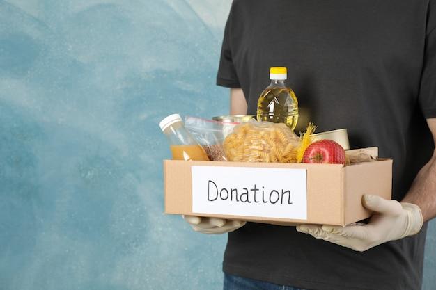 O homem novo mantém a caixa da doação contra o espaço azul. voluntário