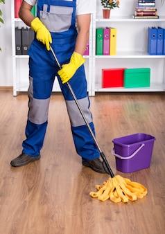 O homem novo no uniforme azul está limpando o assoalho.