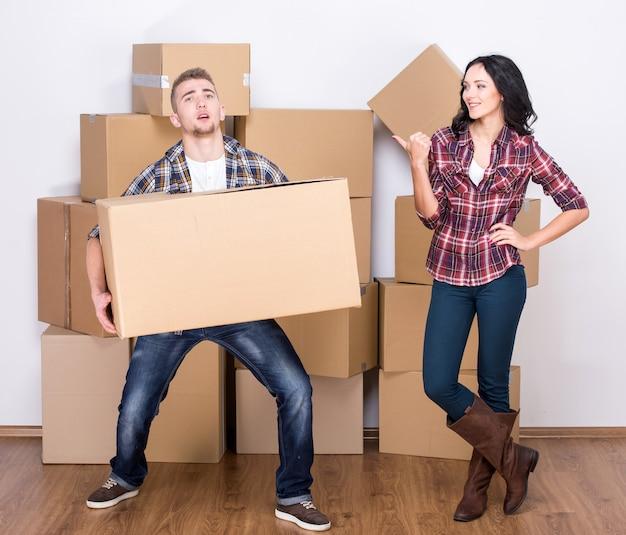 O homem novo pegou uma caixa pesada, mulher que ri.