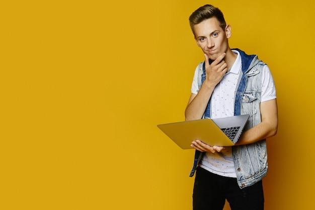 O homem novo pensativo no equipamento ocasional está guardando um portátil e está olhando in camera no fundo amarelo, isolado. conceito de trabalhador remoto.