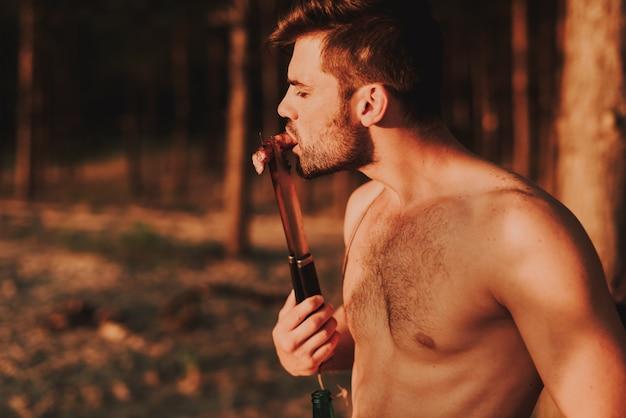 O homem novo prova a salsicha grelhada do fórceps.