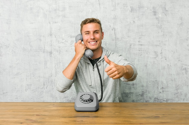 O homem novo que fala em um telefone do vintage com polegares levanta, felicidades sobre algo, apoia e respeita o conceito.