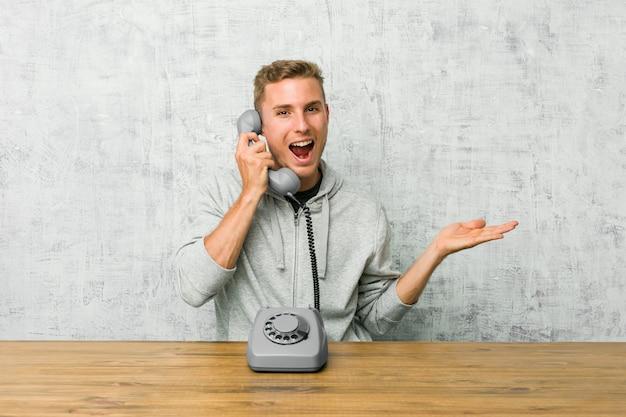 O homem novo que fala em um telefone do vintage prende o espaço da cópia em uma palma, mantenha mão sobre a bochecha.