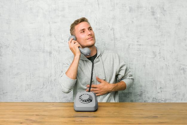 O homem novo que fala em um telefone do vintage toca na barriga, sorri delicadamente, comendo e conceito da satisfação.