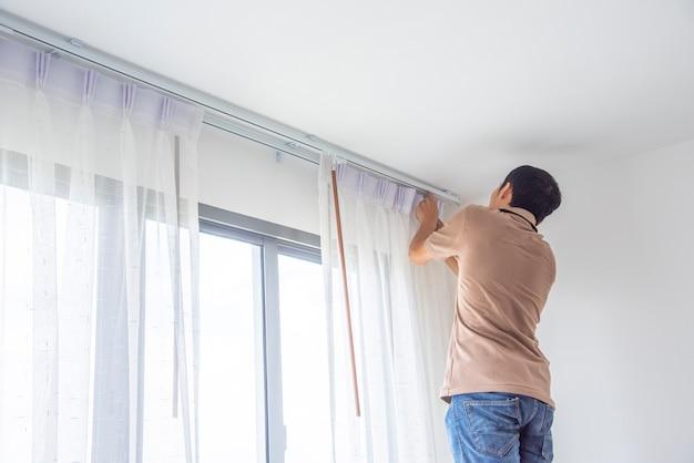 O homem novo que instala cortinas cegas sobre a janela renova dentro da casa.
