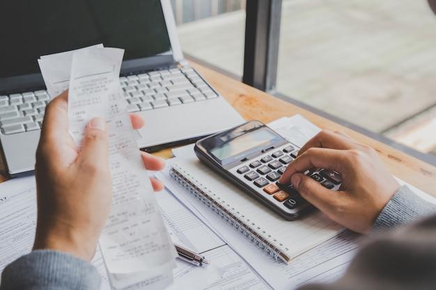 O homem novo que usa a calculadora e calcula contas no escritório domiciliário.