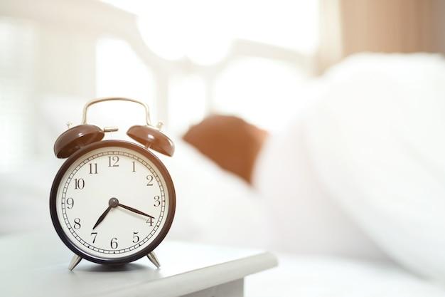 O homem odeia acordar de manhã cedo. menina com sono olhando para o despertador e tentando se esconder debaixo do travesseiro