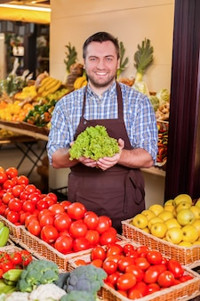 O homem oferece salada fresca.