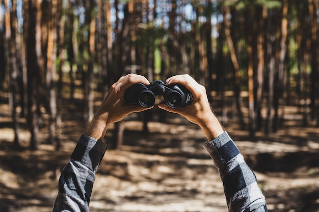 O homem olha através de binóculos contra o da floresta.