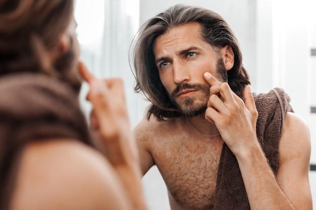 O homem olha cuidadosamente para seu reflexo no espelho, cuidados com a pele