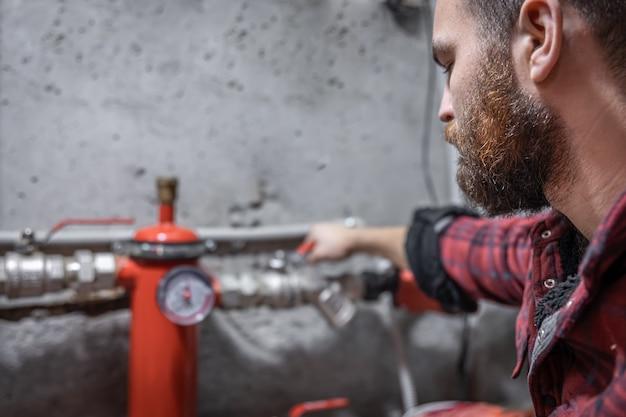 O homem olha para a torneira, canos, válvula, medidor de pressão.