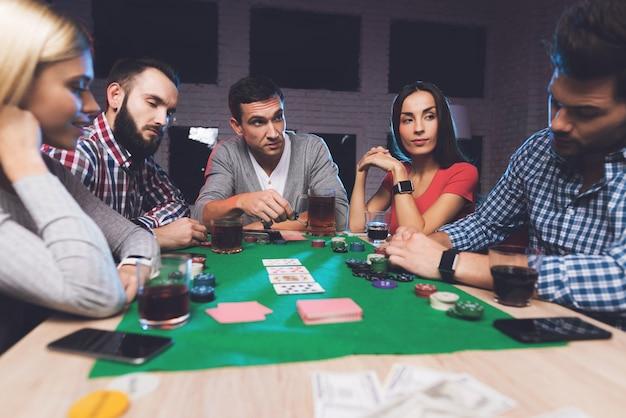 O homem olha para as cartas e todo mundo está esperando ele apostar