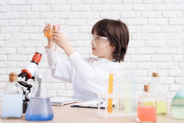O homem olha para as reações químicas no frasco