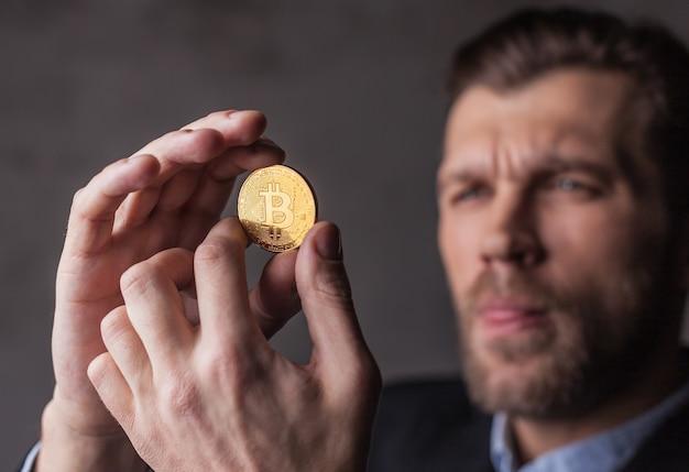 O homem olha para o bitcoin em suas mãos. foco na moeda