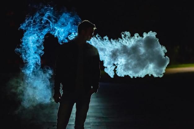 O homem parado na fumaça no fundo escuro. noite noite