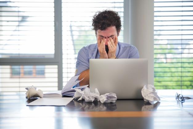 O homem parece cansado enquanto trabalha