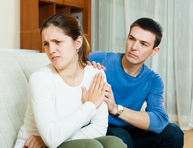 O homem pede perdão da mulher após discussão