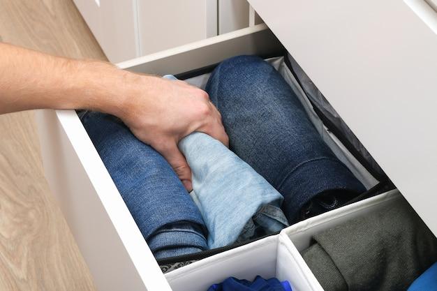 O homem pega calças dobradas pelo método de marie kondo. armazenamento vertical de roupas em uma cômoda. organização de armazenamento. ordem e limpeza. precisão.