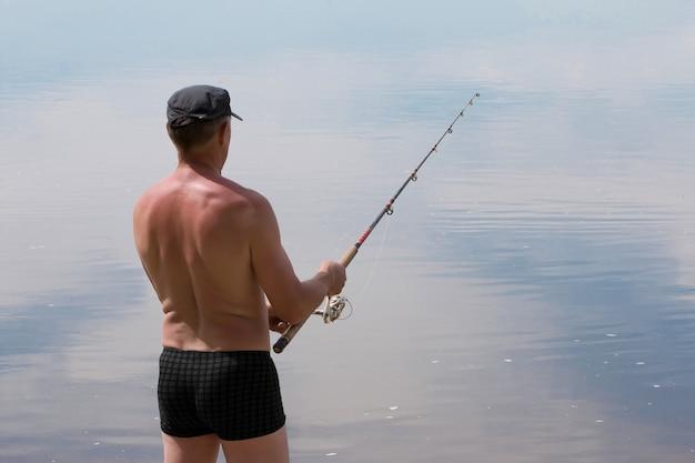 O homem pega peixe girando em um dia quente de verão na lagoa do rio