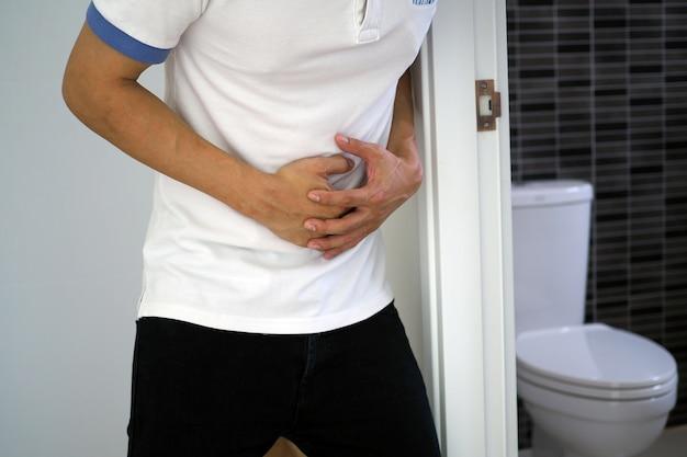 O homem pegou seu estômago e teve uma dor de estômago dolorosa no banheiro. quer merda
