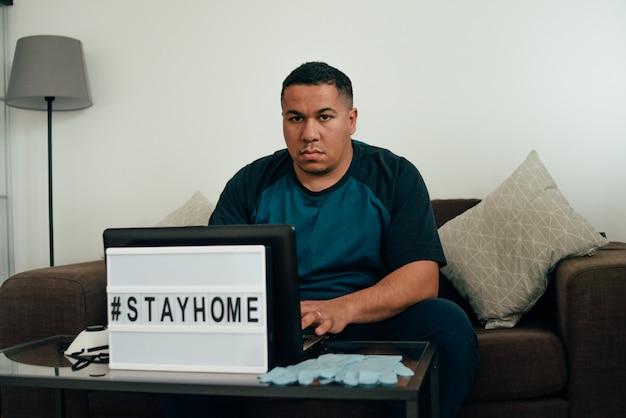 O homem pensa em como parar a propagação do coronavírus. a hashtag fica em casa.