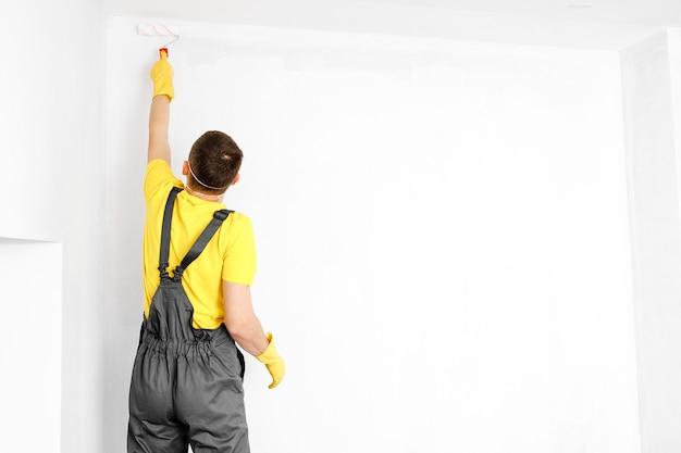 O homem pinta as paredes e o teto na cor branca pintura e reparo da sala.