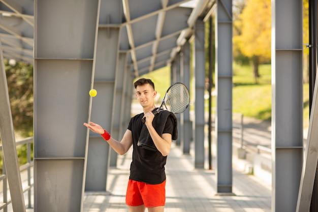 O homem posa ao ar livre com uma raquete de tênis e uma bola. uma toalha está pendurada no ombro dele.