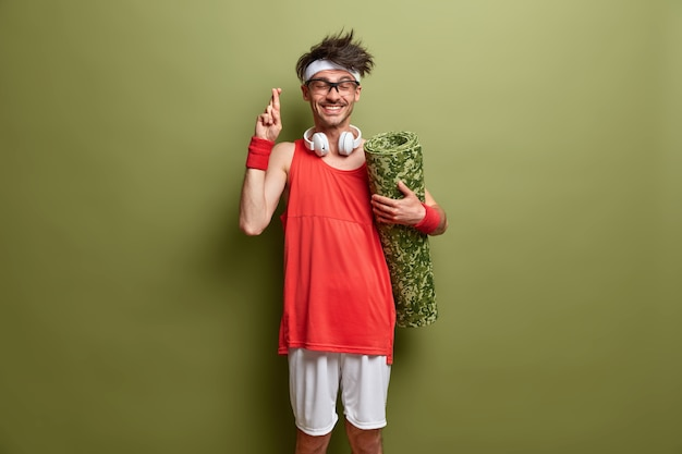 O homem positivo e esperançoso cruza os dedos e acredita no treinamento bem-sucedido, se prepara para o treino, segura o karemat, usa roupas esportivas, tem uma expressão alegre isolada na parede verde. hora do esporte