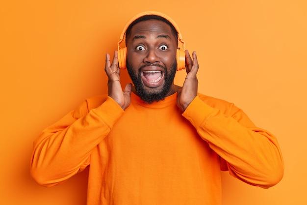 O homem positivo parece surpreendentemente na frente sendo entretido ouve música favorita através de fones de ouvido estéreo surpreso com algo usando um macacão de manga comprida isolado sobre uma parede laranja