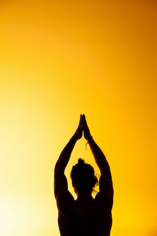 O homem praticando ioga na luz do sol