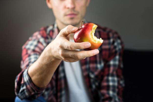 O homem prende a maçã