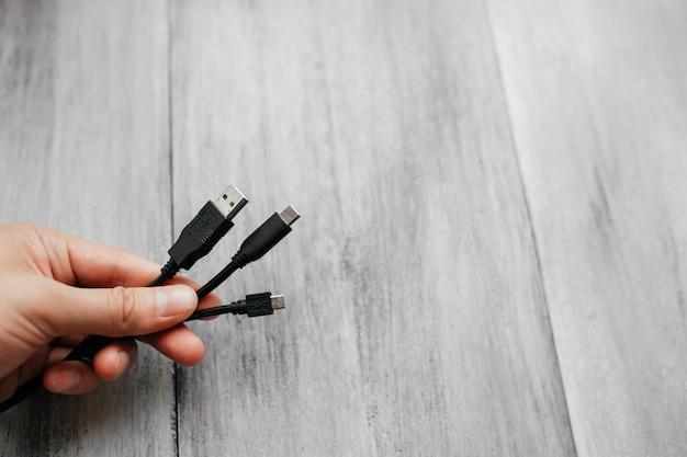 O homem prende cabos usb diferentes com conectores diferentes em um fundo branco de madeira