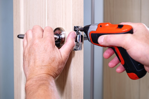 O homem prende o parafuso solto com uma chave de fenda elétrica.
