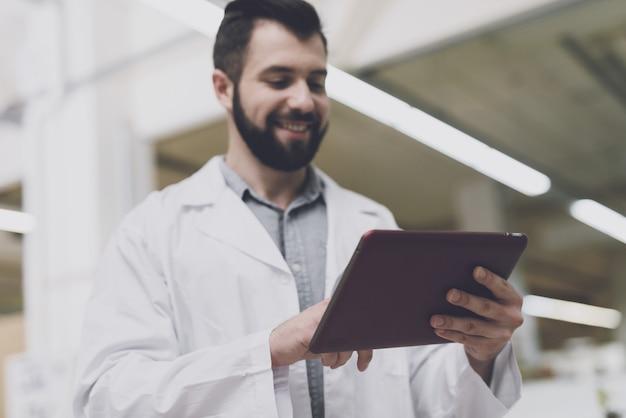 O homem prende o tablet em suas mãos e olha para ele.