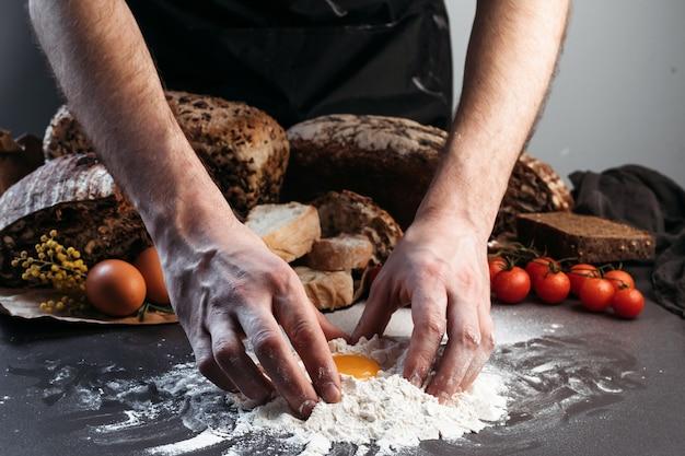 O homem prepara massa para pão, sem glúten e sem produtos de origem animal. pão, sem glúten e sem produtos de origem animal.