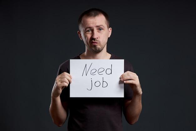 O homem procura trabalho, desemprego e crise. emoções diferentes no rosto, um sinal nas mãos