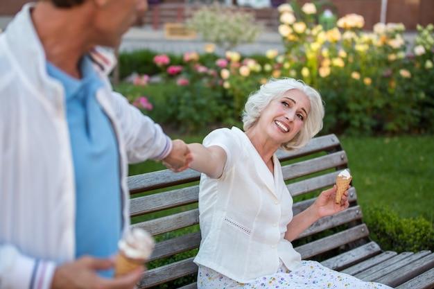 O homem puxa a mão de uma mulher madura.