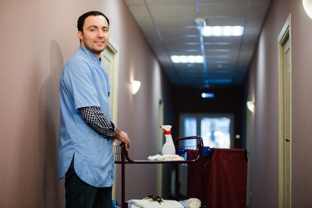 O homem que está no pessoal da equipe de limpeza do hotel está sorrindo com um aspirador de pó no processo de limpeza dos quartos do hotel e entrega de serviço de primeira qualidade aos hóspedes.
