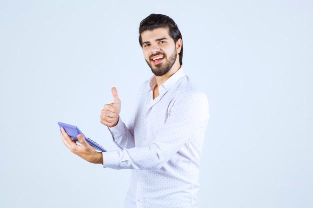 O homem que trabalha com a calculadora parece bem-sucedido e satisfeito.