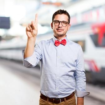O homem que veste um laço vermelho. fazendo um gesto número.