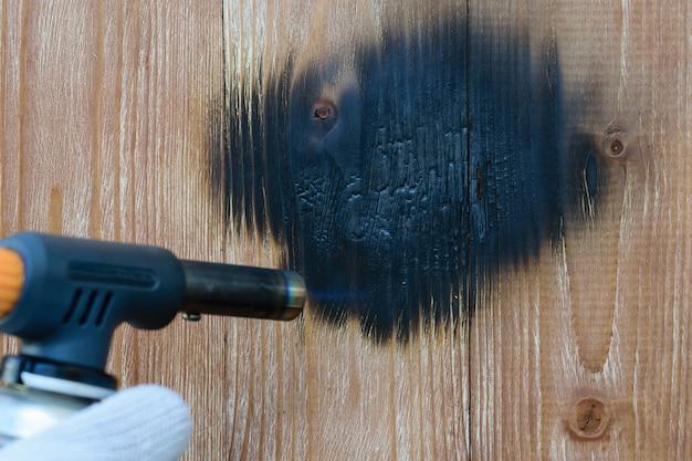 O homem queima placas de madeira do queimador de gás para o processamento do vintage. t
