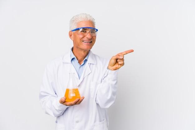 O homem químico maduro isolou o sorriso e apontar de lado, mostrando algo no espaço em branco.
