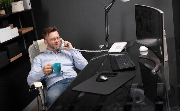 O homem recostou-se na cadeira, tomando café e falando no telefone fixo