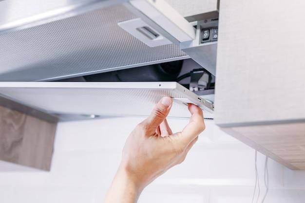 O homem repara a capa na cozinha. filtro de substituição no exaustor