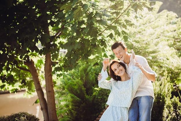 O homem ri sentado com sua senhora no banco de madeira fora
