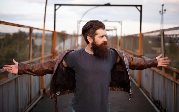 O homem roqueiro com uma longa barba e bigode em uma jaqueta de couro marrom ergueu os braços para os lados e olhou para longe