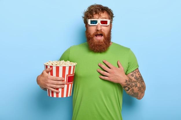 O homem ruivo emocional olha assustado, assiste a filmes de terror sozinho no cinema, fica sem fôlego